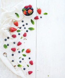 Berry frame with copy space on right  Strawberries  raspberries  blueberries and mint leaves  white wooden background