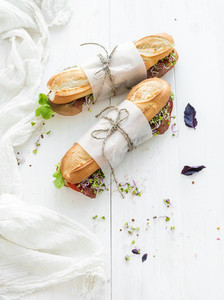 Sandwiches with beef  fresh vegetables and herbs over white wood backdrop  copy space