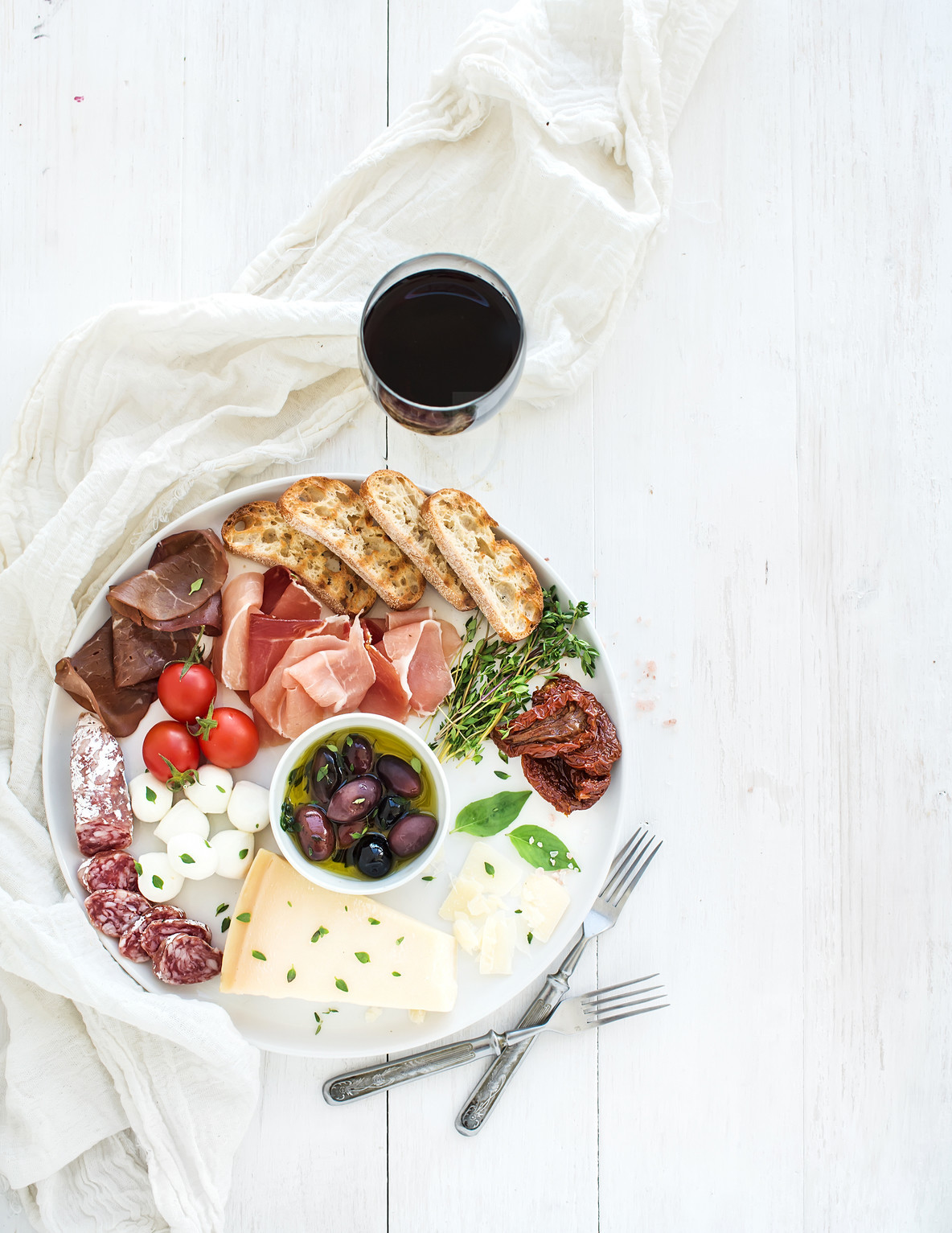 Wine appetizer set  Cherry tomatoes  parmesan cheese  meat variety  bread slices  dried tomatoes  olives and basil on round ceramic plate over white wood backdrop