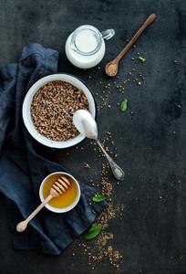 Rustic healthy breakfast set  Cooked buckwheat groats with milk and honey on dark grunge backdrop