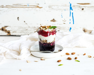 Yogurt oat granola with berries  honey and nuts in glass jar  rustic white  background
