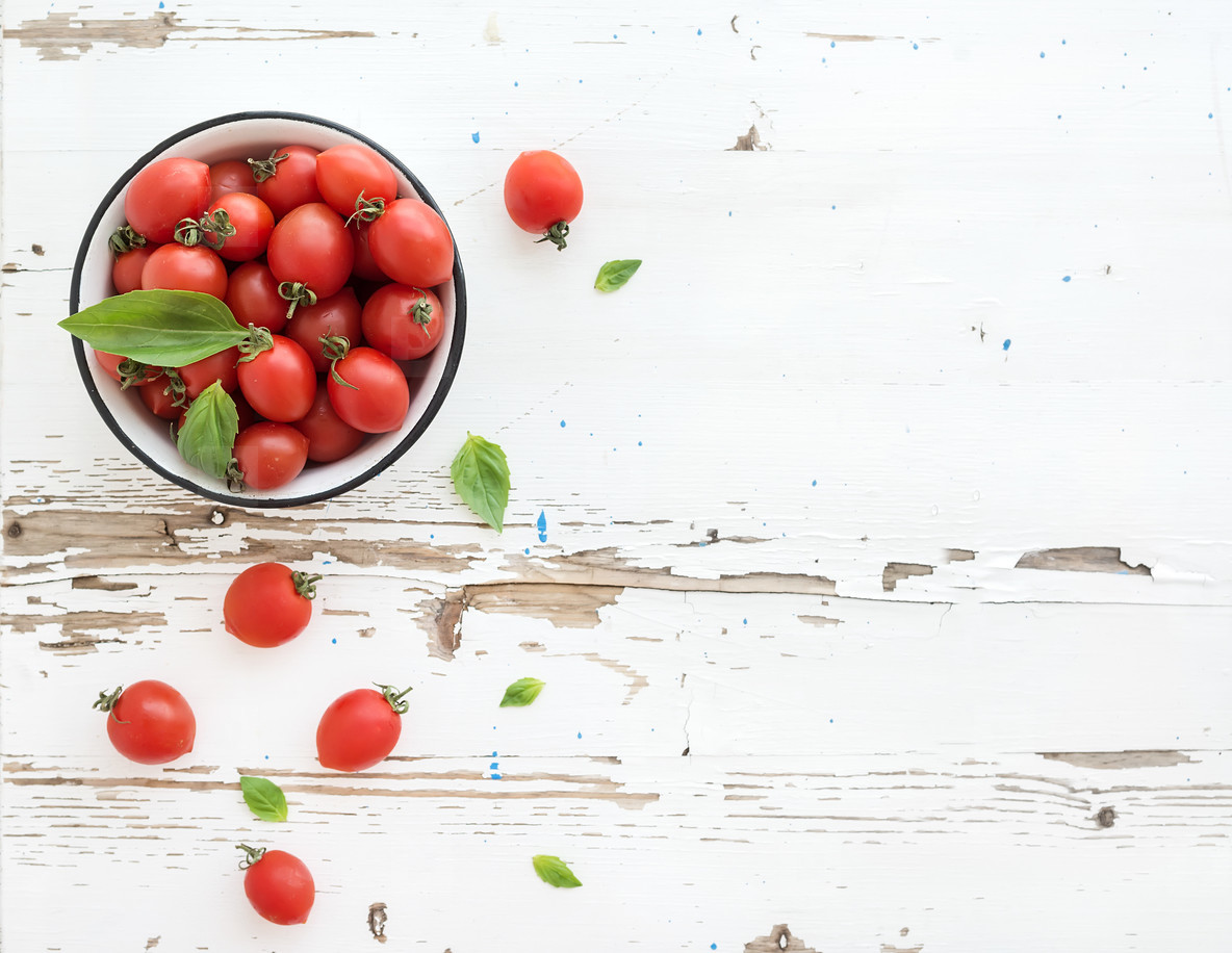 Cherry tomatoes in metal bowl and fresh basil leaves on rustic white wooden backdrop  top view