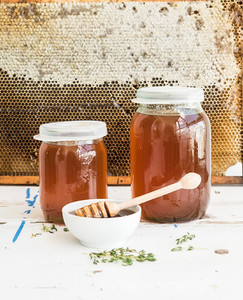 Jars of honey on white rustic wooden table with honeycombs at the backdrop