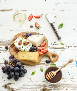Cheese appetizer selection or wine snack set  Variety of cheese  grapes  pecan nuts  strawberry and honey on round wooden board over rustic white backdrop