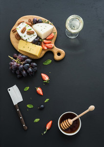 Cheese appetizer selection or whine snack set Variety of cheese grapes pecan nuts strawberry and honey on round wooden board over black backdrop top view