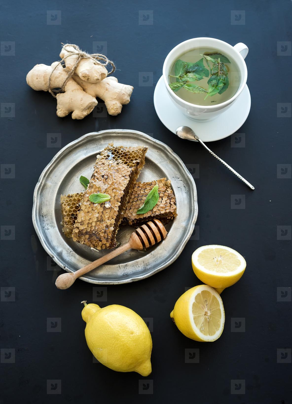 Cup of herbal tea with fresh mint  honey  lemon  ginger on grunge black  background