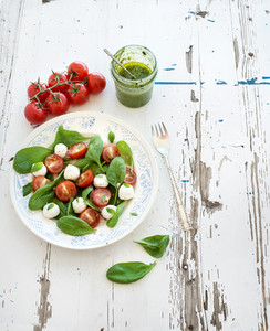 Caprese salad  homemade pesto sauce  Cherry tomatoes  baby spinach and mozzarella in ceramic plate on rustic white wooden backdrop  top view