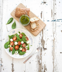 Caprese salad chiabatta slices homemade pesto sauce Cherry tomatoes baby spinach and mozzarella in ceramic plate on rustic white wooden backdrop top view