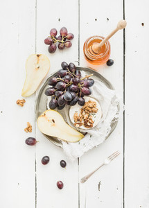 Camembert cheese with grape  walnuts  pear and honey on vintage metal plate over white rustic wood backdrop