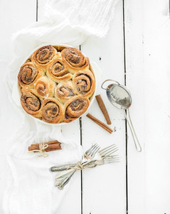 Freshly baked cinnamon buns in dish on a rustic wooden table top view