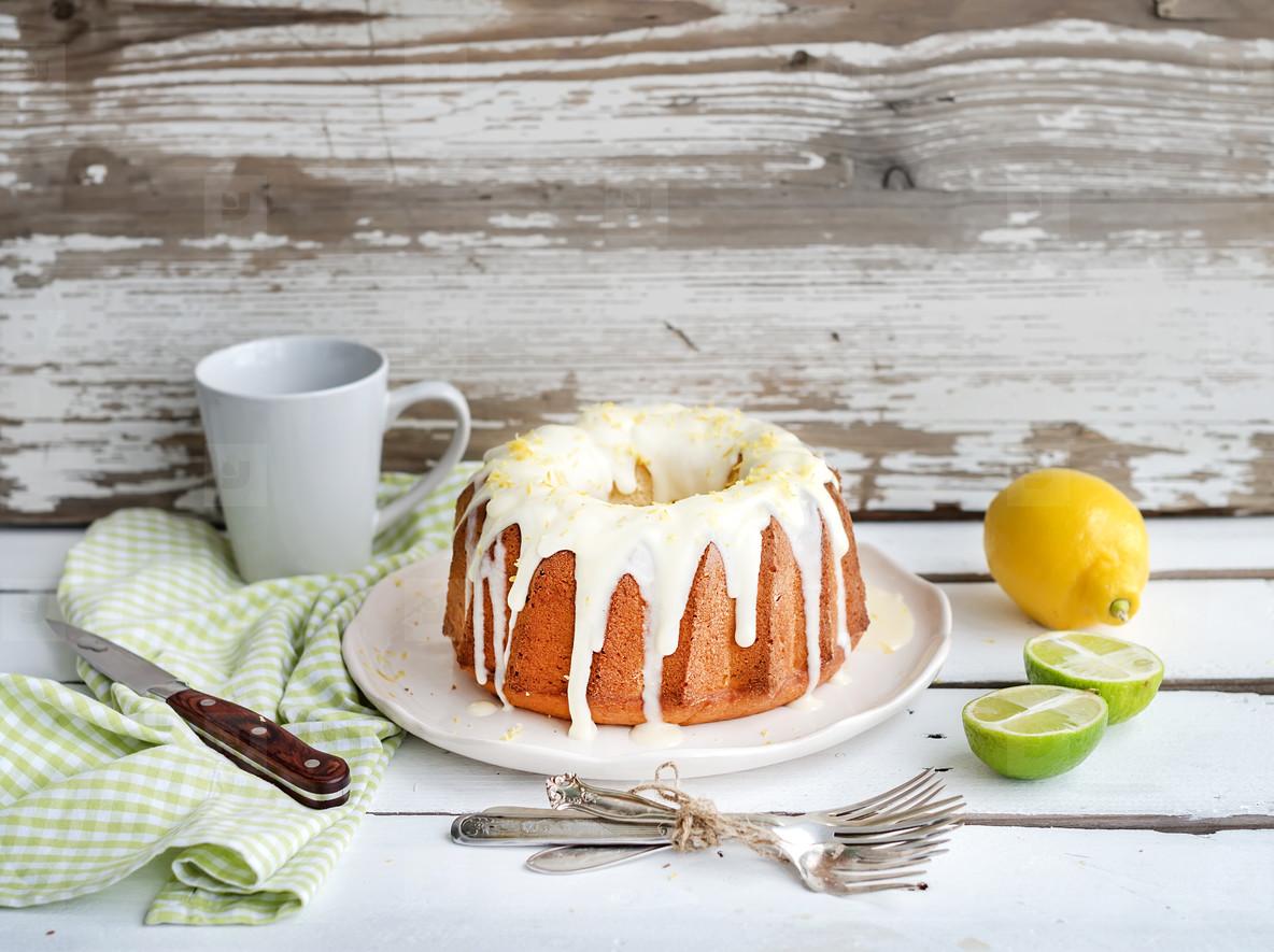 Moist lime and lemon bundt yoghurt cake, white rustic wooden background