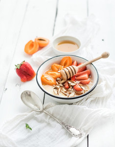 Healthy breakfast set  Rice cereal or porridge with fresh strawberry  apricots  almond and honey over white rustic wood backdrop  top view
