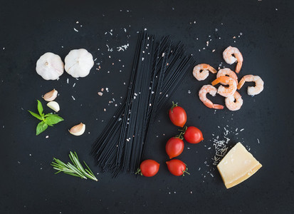 Ingredients for black pasta with seafood  Shrimps  spaghetti  basil  garlic  spices  parmesan cheese and  cherry tomatoes on dark grunge backdrop