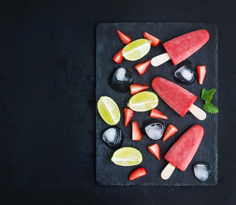 Strawberry and lime ice creams or popsicles with fresg cut berries  citruses  ice cubes  melissa leaves on black slate tray over dark grunge backdrop  top view