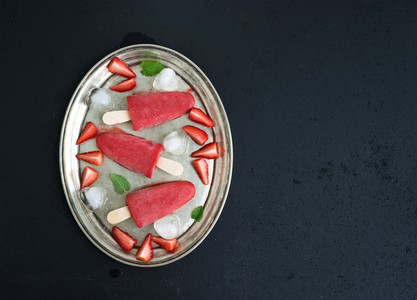 Strawberry ice creams or popsicles with fresh berries  ice cubes and melissa leaves on vintage silver tray over dark grunge backdrop  top view