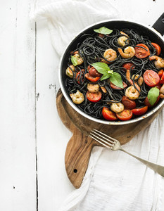Black pasta spaghetti with shrimps basil pesto sauce and slow roasted cherry tomatoes in cooking pan on rustic chopping board over white wooden table