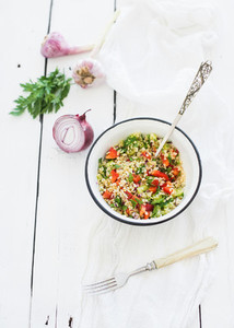 Healthy bulgur salad with paprika red onion parsley and garlic in rustic metal bowl Vintage silverware white wooden backdrop top view