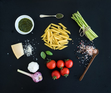Ingredients for cooking pasta  Penne  green asparagus  basil  pesto sauce  garlic  spices  parmesan cheese and  cherry tomatoes on dark grunge backdrop