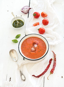 Gazpacho soup in rustic metal bowl with fresh tomatoes green sauce chili garlic and basil over white wooden backdrop