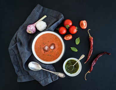 Gazpacho soup in rustic metal bowl with fresh tomatoes green sauce chili garlic and basil over dark grunge backdrop
