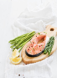 Raw salmon steak with asparagus  lemon  spices and rosemary on rustic wooden chopping board over white backdrop