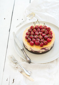 Cheesecake with fresh cherry in ceramic plate over white rustic wooden background