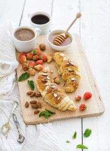 Freshly baked almond croissants with garden strawberries  mint  honey and coffee on serving board over white rustic wood backdrop