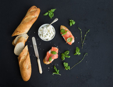 Salmon  ricotta and basil sandwiches with baguette over black grunge background  Top view