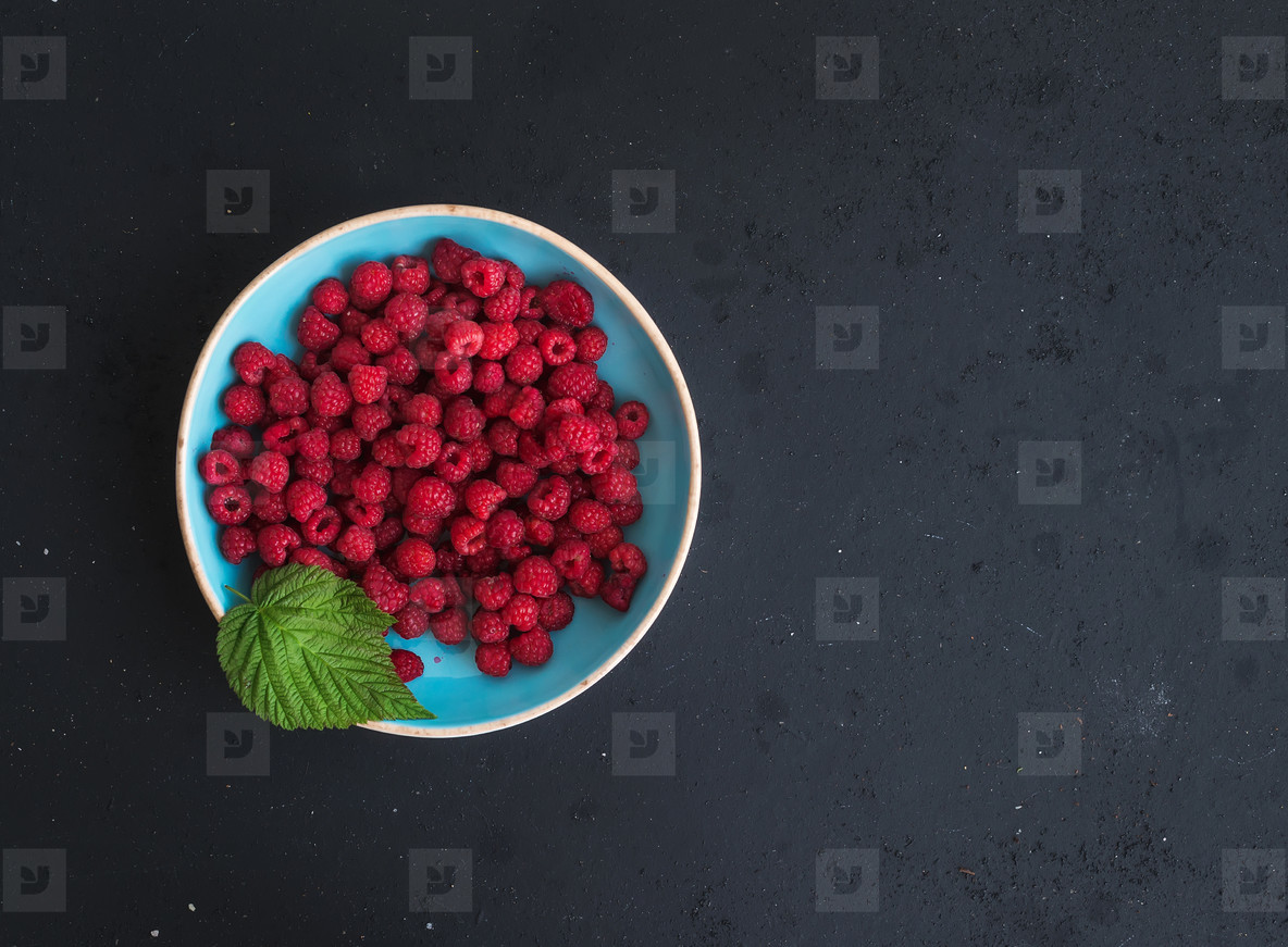 Fresh garden raspberries in blue ceramic bowl over grunge black background  top view