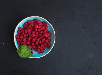 Fresh garden raspberries in blue ceramic bowl over grunge black background  top view