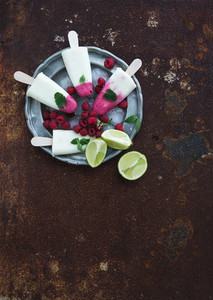 Raspberry lime yougurt ice creams or popsicles with fresh berries and ice cubeson vintage silver plate over grunge metal backdrop  top view