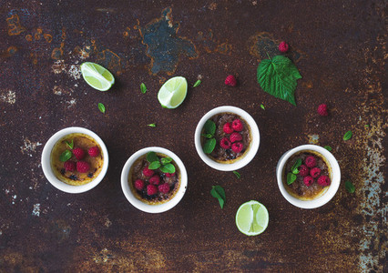 Creme brulees with raspberries and mint in white bowls over grunge metal backdrop Top view