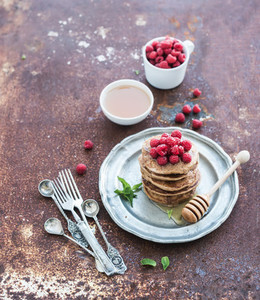 Breakfast set  Buckwheat pancakes with fresh raspberries  honey and mint leaves over grunge metal background