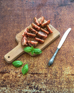 Ripe kumato tomatoes  basil leaves and knife on a rustic wooden chopping board over grunge rusty metal backdrop