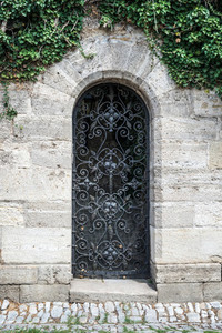 Old medieval black metal door with cerved bar and light stone wall