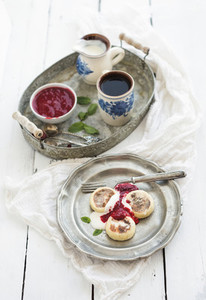 Rustic breakfast set Russian cottage cheese pancakes or syrniki on a vintage metal plate with raspberry jam sour cream and coffee Rustic white backdrop