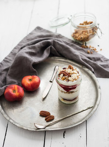 Yogurt oat granola with berries  honey  nuts and nectarins in glass jar on vintage metal tray over rustic white  background