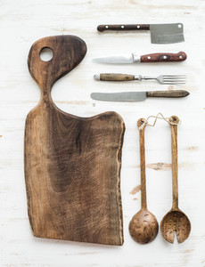 Kitchen ware set Old rustic chopping board made of walnut wood knives fork and salad spoons on a white background