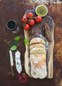 Freshly baked ciabatta bread with cherry tomatoes salami pesto sauce basil and glass of red wine on walnut wood board over grunge rusty metal background top view