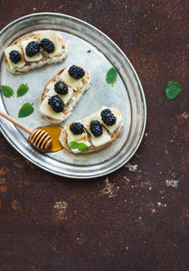 Italian bruschetta sandwich with brie cheese  honey and blackberry on vintage silver tray over grunge rusty metal background  top view