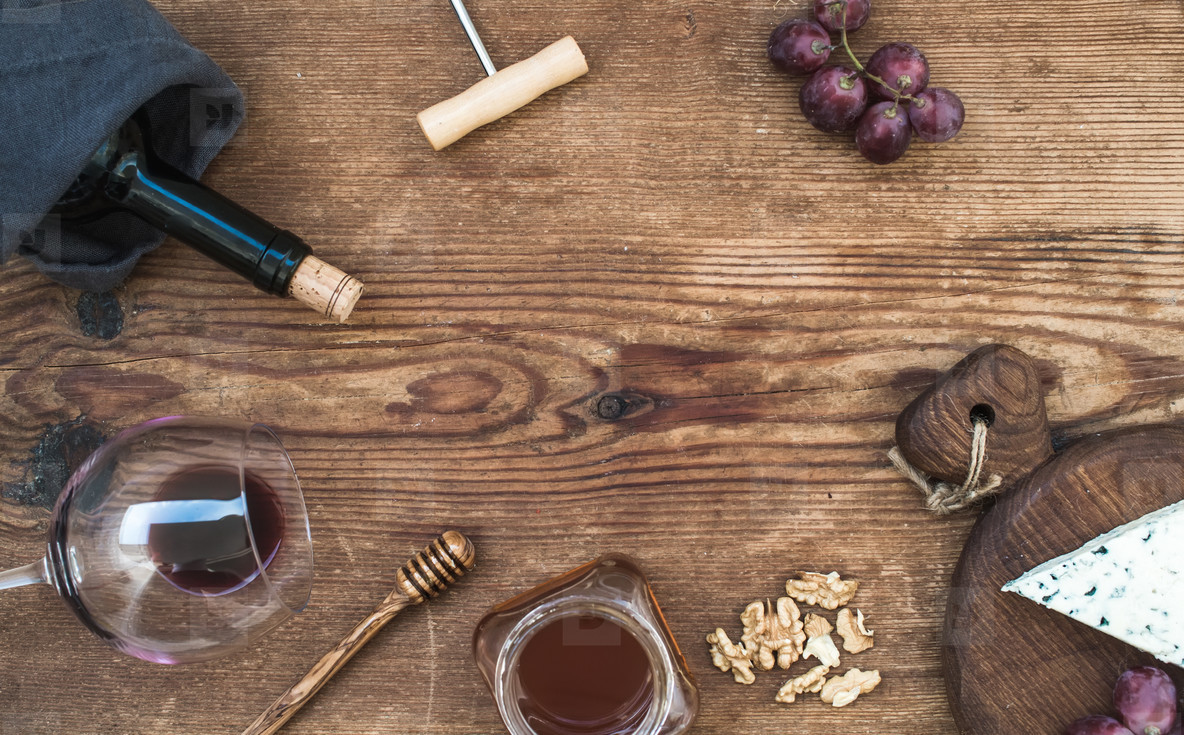Wine and appetizer set with copy space in center  Glass of red wine  bottle  corkscrewer  blue cheese on serving board  grapes  honey  walnuts over rustic wooden table  top view