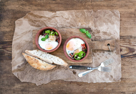 Country style breakfast set  Eggs baked in separate clay cups with tomatoes  peppers  fresh basil  bread slices on rustic board over oily craft paper and wooden background  top view