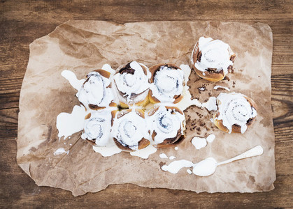 Cinnamon rolls with cream cheese icing on piece of oily craft paper over rustic wooden background