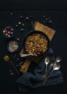 Healthy breakfast  Oat granola crumble with frozen fresh berries  and seeds in irom skillet pan on rustic wooden board over dark backdrop