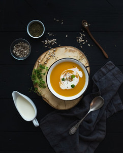Pumpkin soup with cream  seeds and spices in rustic metal bowl over grunge black background  Top view