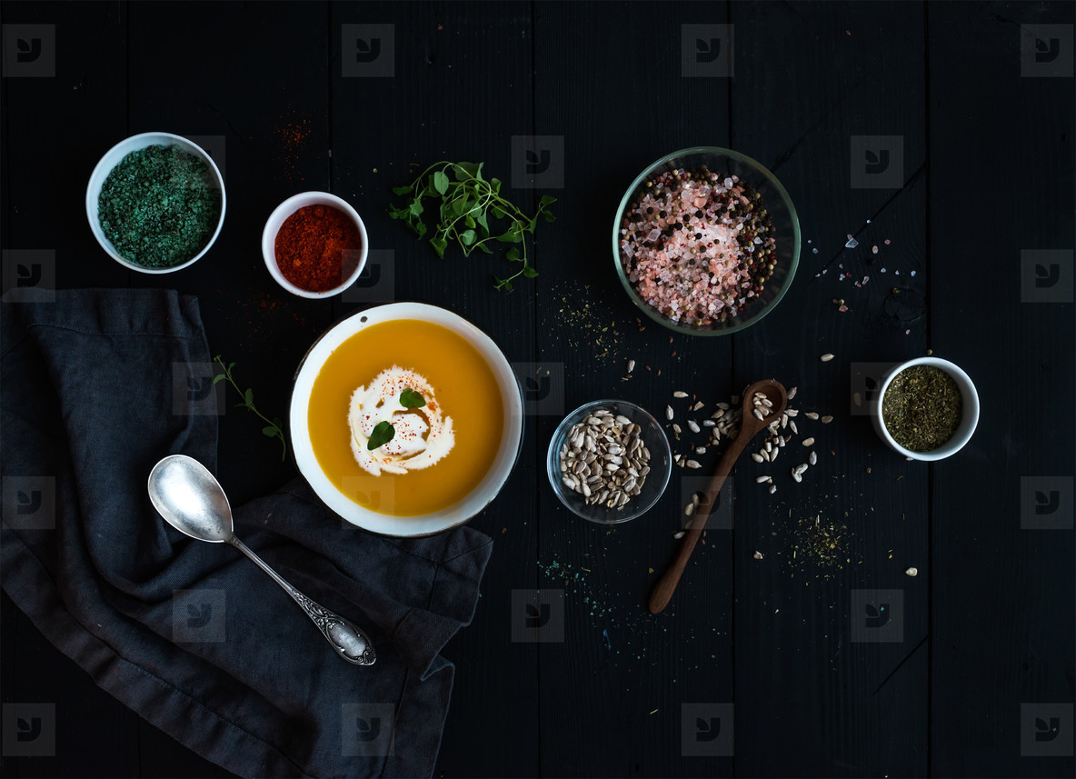 Pumpkin soup with cream  seeds and various spices in rustic metal bowl over grunge black background  Top view