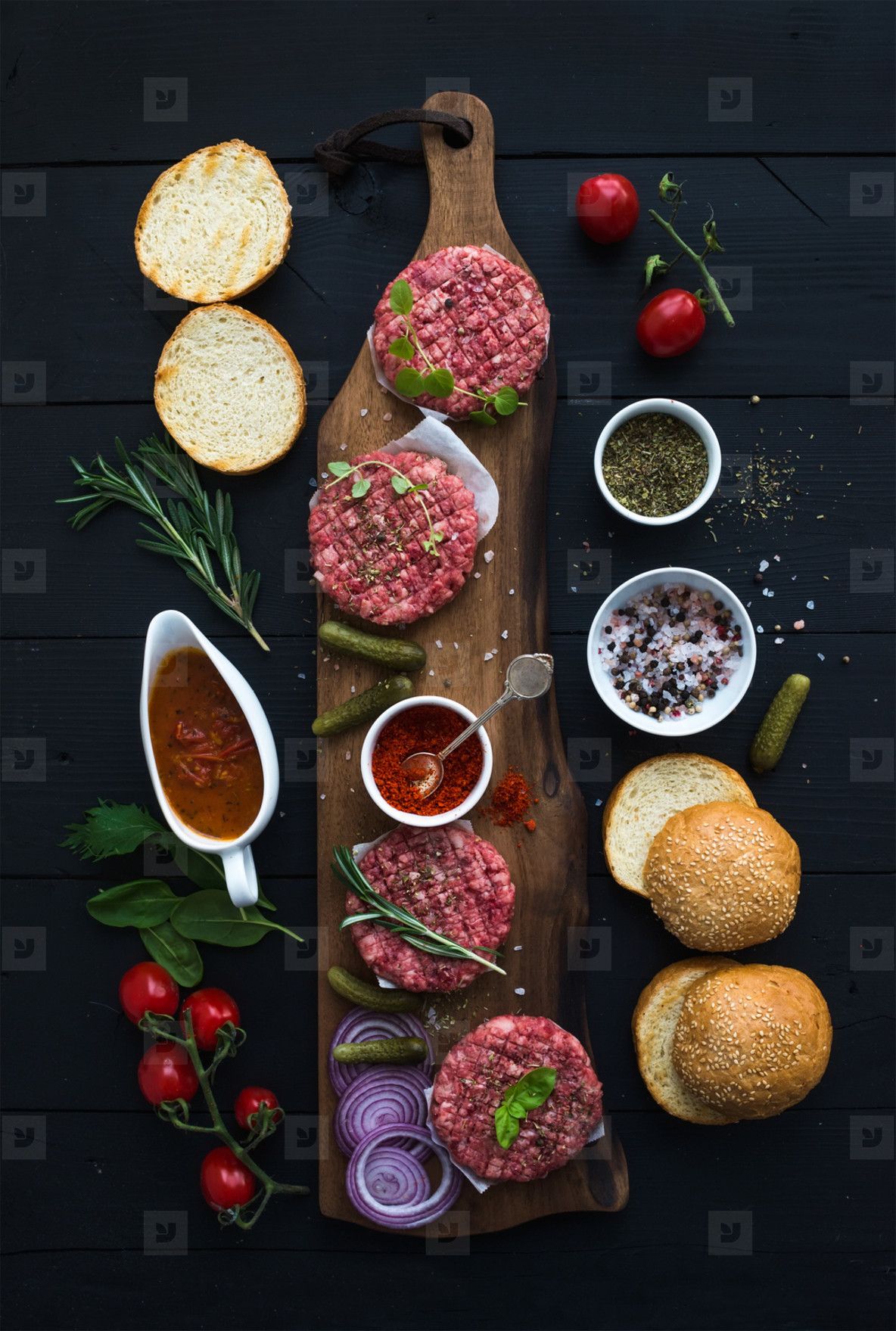 Ingredients for cooking burgers  Raw ground beef meat cutlets on wooden board  red onion  cherry tomatoes  greens  pickles  tomato sauce  cheese  herbs and spices over black background  top view