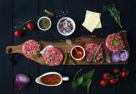 Ingredients for cooking burgers  Raw ground beef meat cutlets on wooden chopping board  red onion  cherry tomatoes  greens  pickles  tomato sauce  cheese  herbs and spices over black background  top v