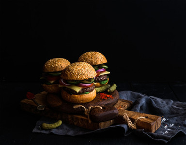 Fresh beef burgers with pickles and spices on rustic wooden boards  black background