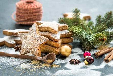 Cooked Christmas holiday traditional gingerbread cookies with sugar powder  anise and cinnamon sticks on black background